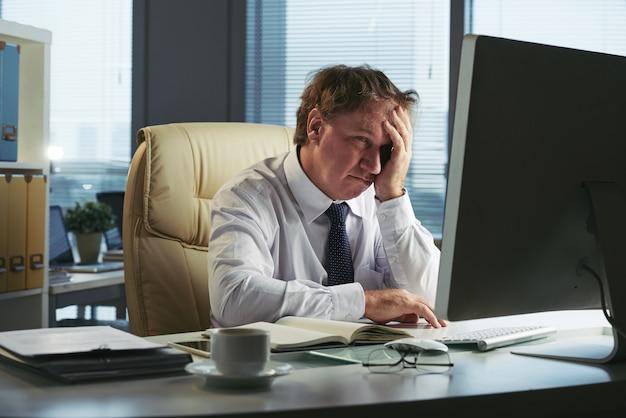 Betonter mann mit den kopfschmerzen, die früh morgens in seinem büro arbeiten