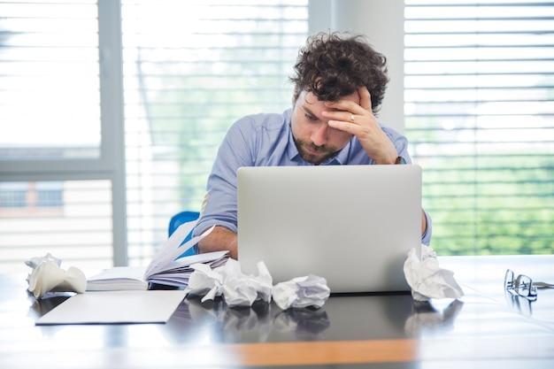 Betonter mann mit laptop im büro