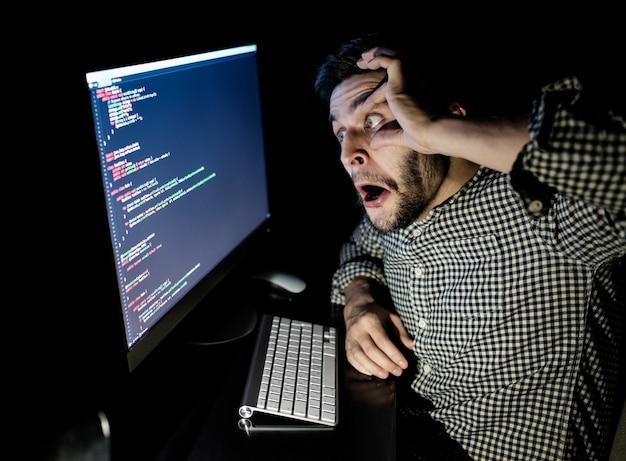 Betonter softwareentwickler mit büro des computers zu hause