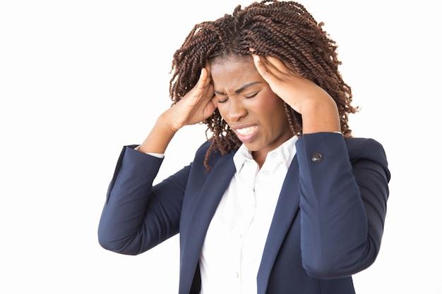Betonter unglücklicher weiblicher angestellter, der unter kopfschmerzen leidet