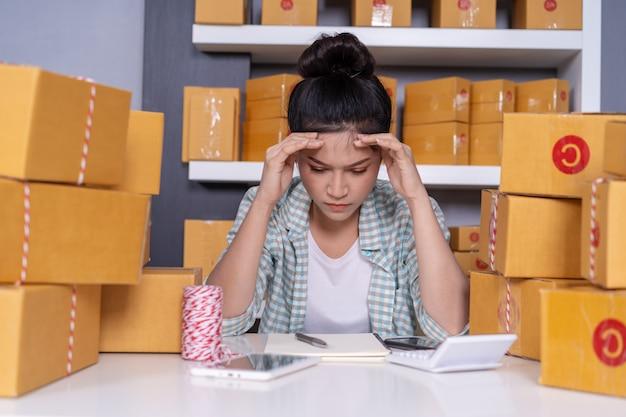 Betontes büro der jungen unternehmerfrau und des kurierpaketpakets zu hause