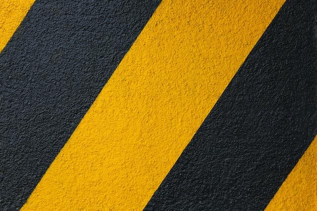 Betonwand mit gelbem und schwarzem diagonalem streifenhintergrund