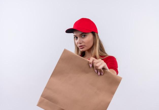 Betrachten der jungen lieferfrau der kamera, die rote uniform und kappe hält, die papiertüte lokalisiert auf weißem hintergrund hält