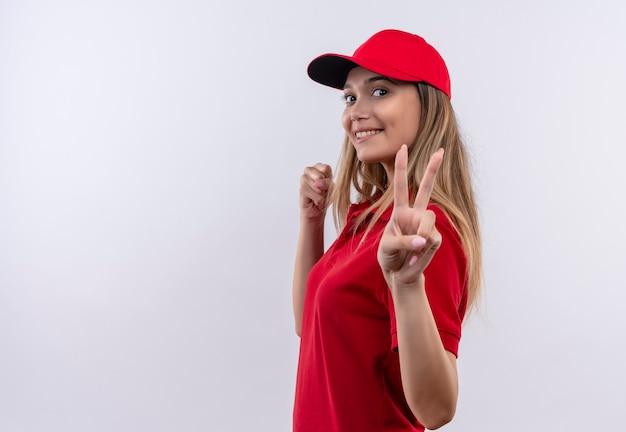 Betrachten der kamera erfreut junges liefermädchen, das rote uniform und kappe zeigt, die friedensgeste lokalisiert auf weißem hintergrund mit kopienraum zeigt