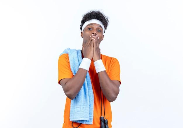 Betrachten der kamera erschreckte jungen afroamerikanischen sportlichen mann, der stirnband und armband bedeckte mund mit händen mit handtuch auf schulter lokalisiert auf weißem hintergrund trägt