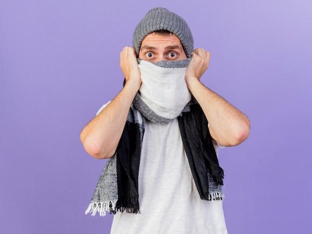 Betrachten der kamera erschreckte jungen kranken mann, der wintermütze mit schal bedeckte gesicht mit schal lokalisiert auf lila hintergrund trägt
