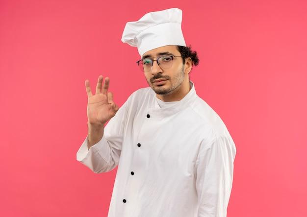 Betrachten der kamera junger männlicher koch, der kochuniform und brille trägt, die okey geste zeigen