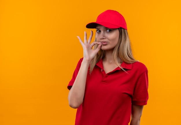 Betrachten der kamera junges liefermädchen, das rote uniform und kappe zeigt, die okey geste lokalisiert auf orange hintergrund zeigt