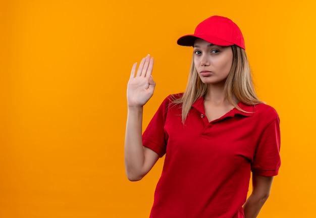 Betrachten der kamera junges liefermädchen, das rote uniform und kappe zeigt stoppgestik lokalisiert auf orange hintergrund