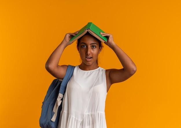 Betrachten der kamera junges schulmädchen, das rückentasche bedeckt kopf mit buch trägt
