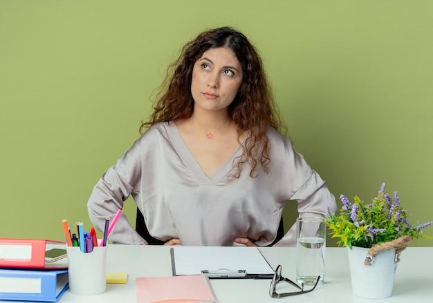 Betrachten der seite denkend junge hübsche weibliche büroangestellte sitzen am schreibtisch mit bürowerkzeugen, die hände auf hüfte lokalisiert auf olivgrünem hintergrund setzen