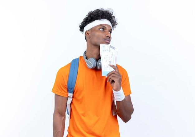 Betrachten der seite denkend junger afroamerikanischer sportlicher mann, der stirnband und armband hält, die tickets lokalisiert auf weißem hintergrund halten
