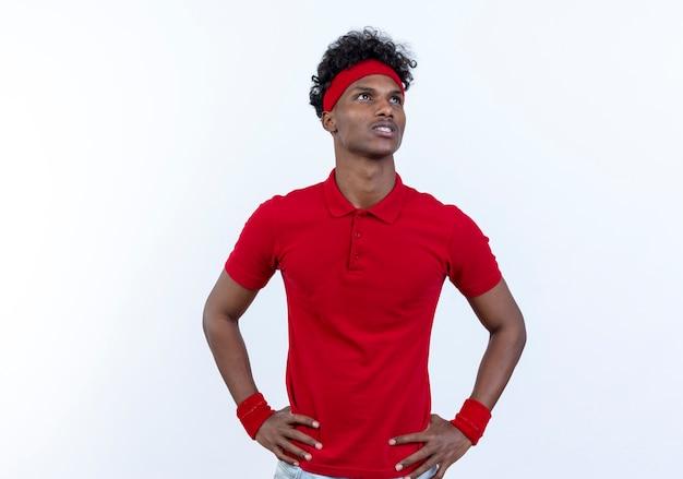 Betrachten der seite denkend junger afroamerikanischer sportlicher mann, der stirnband und armband trägt, die hände auf hüfte lokalisiert auf weißem hintergrund setzen