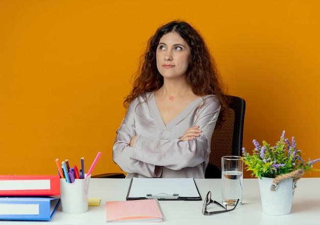 Betrachten der seite denkend junger hübscher weiblicher büroangestellter, der am schreibtisch mit bürowerkzeugen kreuzt, die hände lokalisiert auf orange hintergrund kreuzen