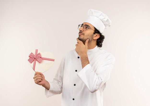 Betrachten der seite denkend junger männlicher koch, der kochuniform und gläser hält, die herzform-geschenkbox halten und hand auf kinn setzen