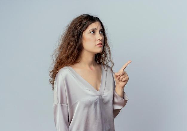 Betrachten der seite traurige junge hübsche weibliche büroangestellte zeigt auf der seite lokalisiert auf weißem hintergrund mit kopienraum
