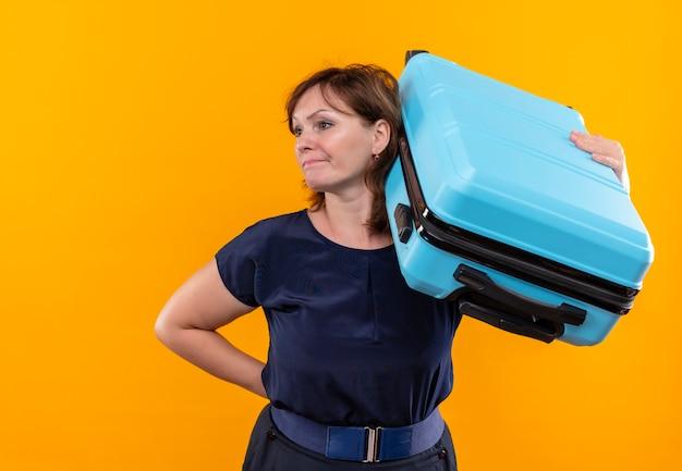 Betrachten der seite verwirrte reisende frau mittleren alters, die koffer auf schulter auf isolierter gelber wand hält