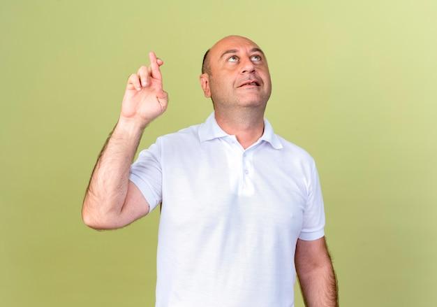 Betrachten des erfreuten reifen mannes, der finger lokalisiert auf olivgrüner wand kreuzt