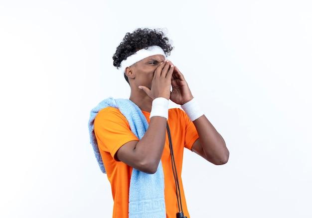 Betrachten des jungen afroamerikanischen sportlichen mannes der seite, der stirnband und armband trägt und jemanden mit handtuch auf schulter lokalisiert auf weißem hintergrund anruft