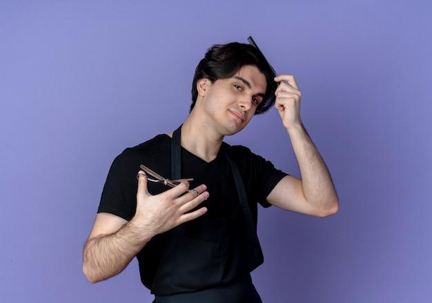 Betrachten des jungen gutaussehenden männlichen friseurs der kamera in der uniform, die haare mit kamm kämmt und schere hält