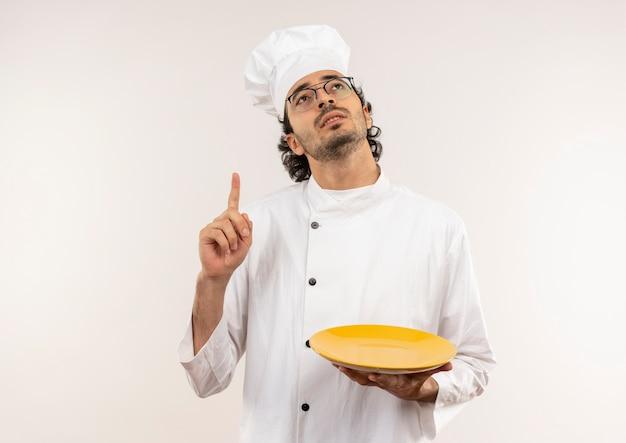 Betrachten des jungen männlichen kochs, der kochuniform und gläser hält platte und zeigt nach oben