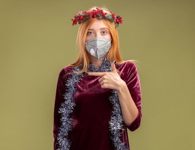 Betrachten des jungen schönen mädchens der kamera, das rotes kleid mit kranz und medizinischer maske mit girlande auf halspunkten an der seite trägt, lokalisiert auf olivgrünem hintergrund mit kopienraum