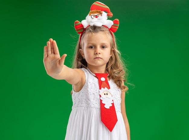 Betrachten des kleinen mädchens der kamera, das weihnachtshaarreifen mit krawatte trägt, die stoppgestik lokalisiert auf grünem hintergrund zeigt