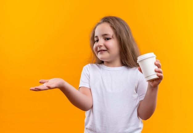Betrachten des kleinen schulmädchens der seite, das weißes t-shirt hält, das tasse kaffee auf isolierter orange wand hält