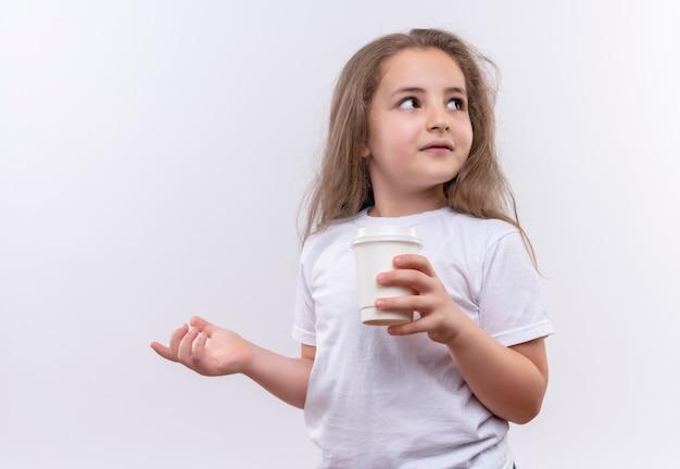 Betrachten des kleinen schulmädchens der seite, das weißes t-shirt hält, das tasse kaffee auf isolierter weißer wand hält