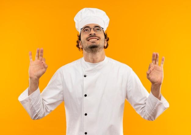 Betrachten des lächelnden jungen männlichen kochs, der die kochuniform und die brille trägt, die okey geste zeigen