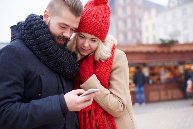 Betrachten des mobiltelefons auf dem weihnachtsmarkt