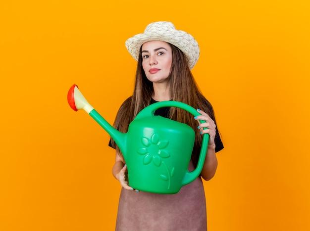 Betrachten des schönen gärtnermädchens der kamera, das uniform und gartenhut trägt