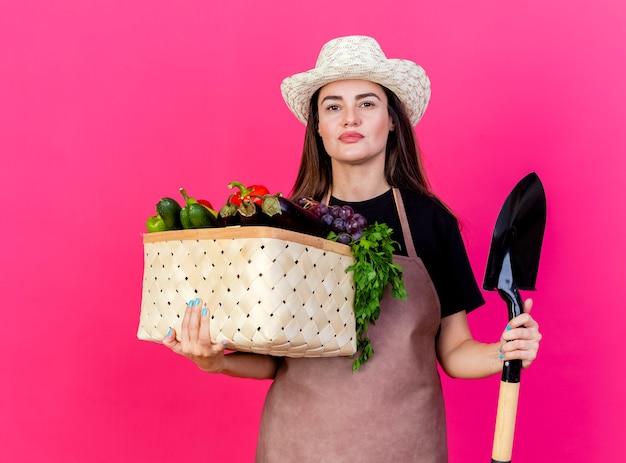 Betrachten des schönen gärtnermädchens der kamera in der uniform, die gartenhut hält, der gemüsekorb mit spaten lokalisiert auf rosa hintergrund hält