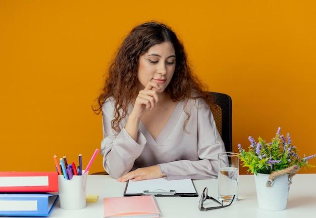 Betrachten des schreibtischdenkens junge hübsche weibliche büroangestellte, die am schreibtisch mit bürowerkzeugen sitzt, die hand unter finger lokalisiert auf orange wand setzen