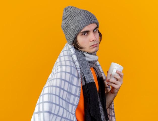 Betrachten des schwachen jungen kranken mannes der kamera, der wintermütze mit schal wickelt, der in plaid eingewickelt tasse tasse tee umwickelt