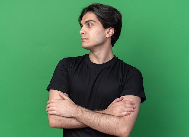 Betrachten des seitlichen jungen gutaussehenden kerls, der schwarze t-shirtkreuzungshände lokalisiert auf grüner wand trägt