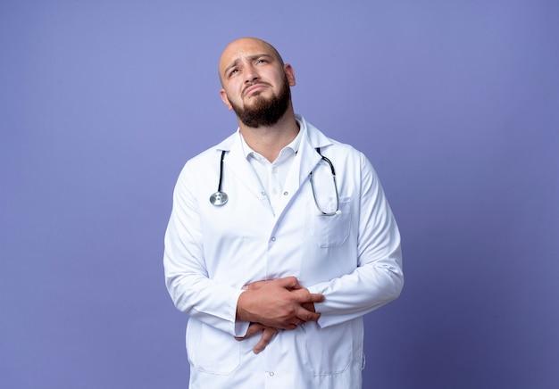 Betrachten des traurigen jungen kahlen männlichen arztes, der medizinische robe und stethoskop hält, die hände zusammen lokalisiert auf blauem hintergrund tragen