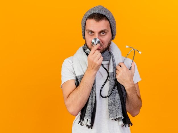 Betrachten des traurigen jungen kranken mannes der kamera, der wintermütze und schal hält und stethoskop auf nase lokalisiert auf gelb hält