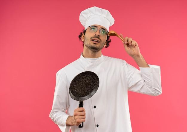 Betrachten des verwirrten jungen männlichen kochs, der die kochuniform und die gläser trägt, die bratpfanne halten und löffel auf die stirn setzen