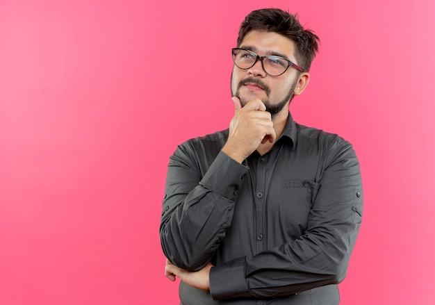 Betrachten nach oben denkender junger geschäftsmann, der brillen trägt, die hand auf kinn lokalisiert auf rosa wand setzen