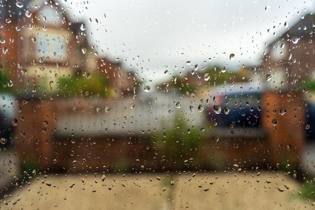 Betrachten sie das gesicht des herbstes durch das von regentropfen bedeckte fensterglas