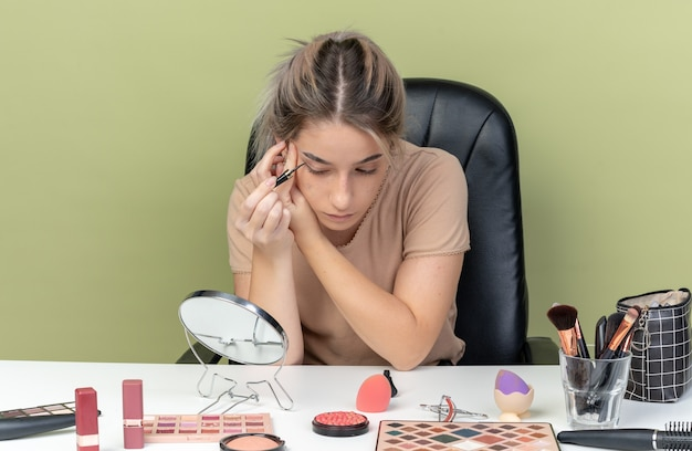 Betrachten sie ein junges schönes mädchen, das mit make-up-tools am tisch sitzt, ziehen sie den pfeil mit dem eyeliner, der auf der olivgrünen wand isoliert ist