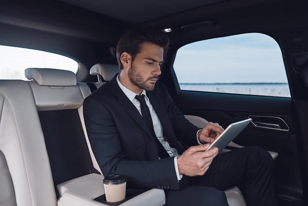 Betrachten wir den nächsten schritt. hübscher junger mann im vollen anzug, der mit digitalem tablet arbeitet, während er im auto sitzt