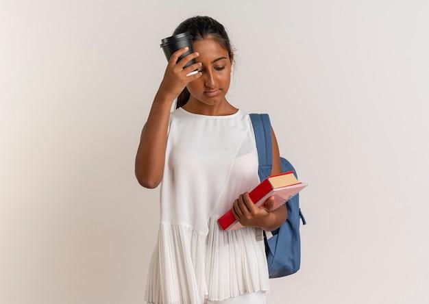 Betrachtet man das junge schulmädchen, das einen rucksack hält, der ein buch mit einem notizbuch hält, und stellt eine tasse kaffee auf die stirn