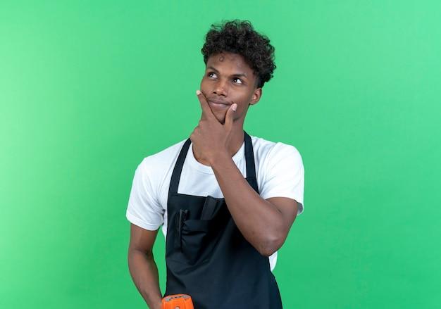 Betrachtet man den seitlich denkenden jungen afroamerikanischen männlichen friseur, der eine uniform trägt, die lautsprecher hält und die hand auf das kinn legt
