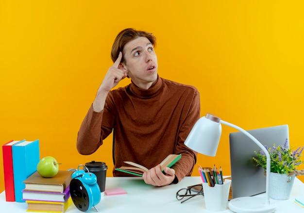 Betrachtet man den seitlich denkenden jungen studentenjunge, der am schreibtisch sitzt?