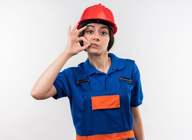 Betrachtet man die kamera junge baumeisterfrau in uniform, die köstliche geste zeigt?