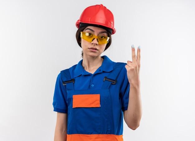Betrachtet man die kamera junge baumeisterin in uniform mit brille, die zwei zeigt? Premium Fotos