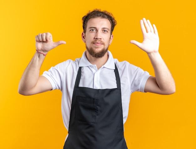 Betrachtet man die kamera junger männlicher friseur in uniform, der verschiedene gesten zeigt, die auf gelber wand isoliert sind?