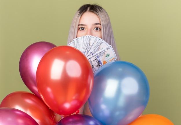 Betrachtet man die kamera junges schönes mädchen bedecktes gesicht mit bargeld, das hinter luftballons steht